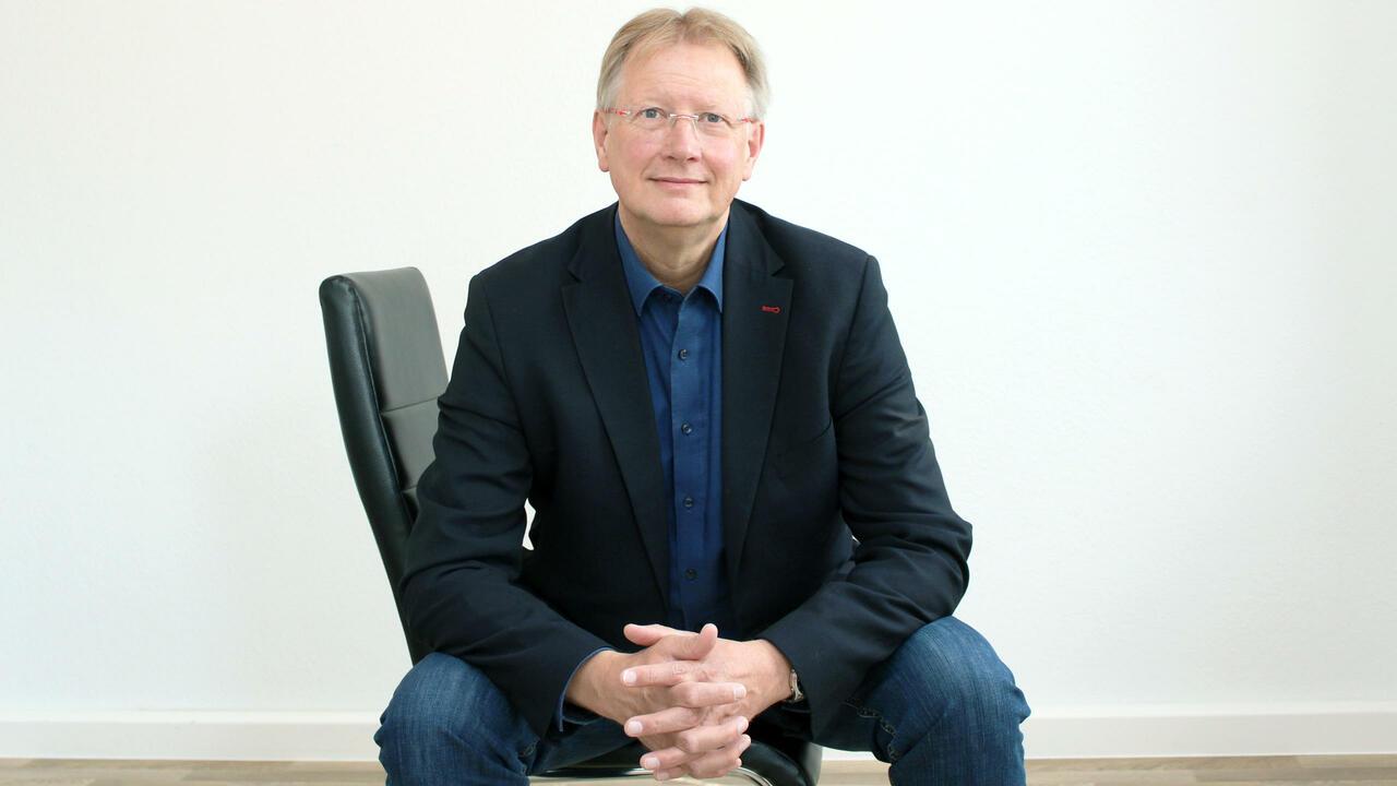 Dr. Thomas Gans sitzt auf einem Bürostuhl und blickt in die Kamera