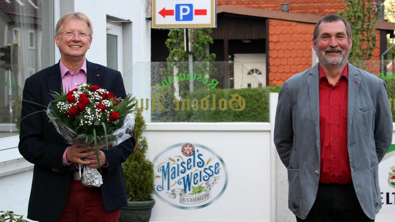 Dr. Thomas Gans und Uwe Speit stehen vor der Goldenen Aue. Thomas Gans hält einen Blumenstrauß.