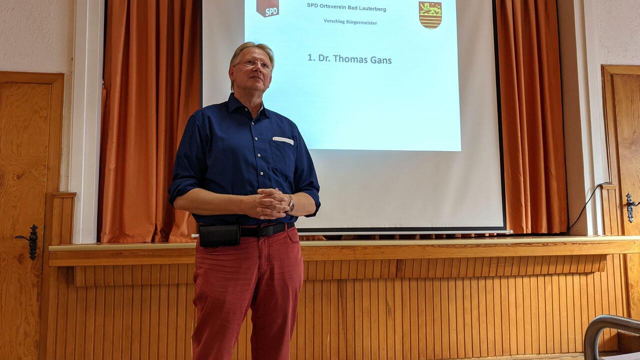 Thomas Gans steht vor der Bühne des Saals der goldenen Aue und hält eine Rede